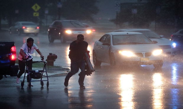 People search for cover as a derecho storm pushes through the area on August 10, 2020 in Chicago, Illinois. The storm, with winds gusts close to 100 miles per hour, downed trees and power lines as it moved through the city and suburbs. (Photo: Scott Olson/Getty Images)