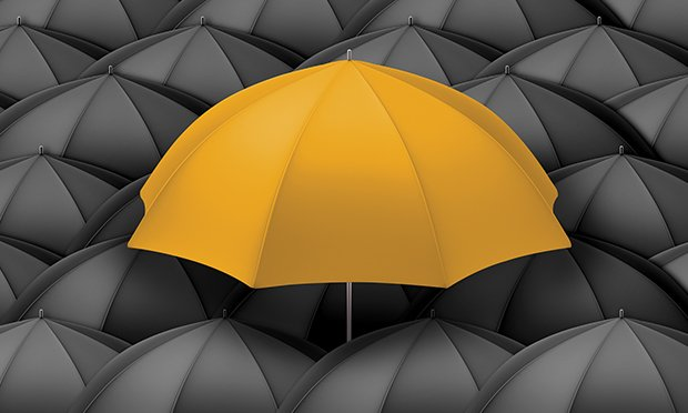 Yellow umbrella in a sea of black umbrellas.