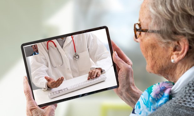 Senior woman consults a e-health doctor with tablet computer sitting in soft chair. In touchscreen, male doctor: With telehealth application patient can reach relevant specialist remotely. (Photo: by JPC-PROD/Shutterstock)