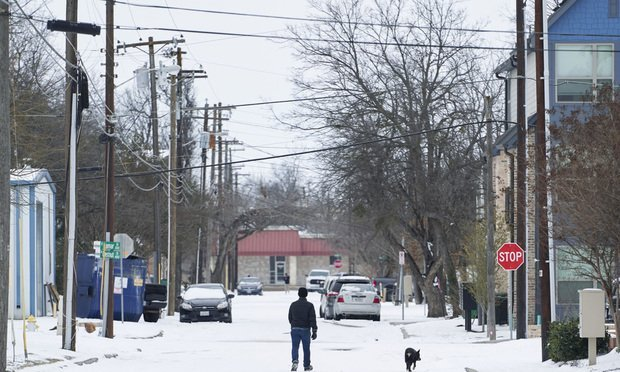 A person walks their dog in McKinney, Texas, on Tues., Feb. 16, 2021. The energy crisis crippled Texas as blackouts left almost millions of people without electricity during the unprecedented freezing weather. (Cooper Neill/Bloomberg)