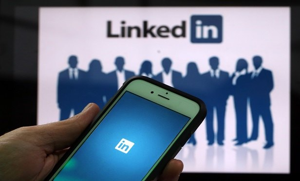 The LinkedIn Corp. logo is displayed on the screens of an Apple Inc. iPhone 6 and a laptop in this arranged photograph taken in London, U.K., on Friday, May, 15, 2015. Facebook Inc. reached a deal with New York Times Co. and eight other media outlets to post stories directly to the social network's mobile news feeds, as publishers strive for new ways to expand their reach. Photographer: Chris Ratcliffe/Bloomberg