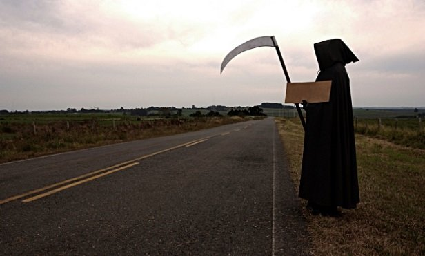 The grim reaper standing by the highway