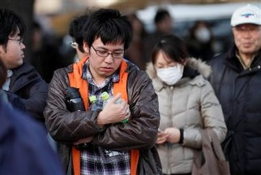 A man holds empty bottles as he waits for water an emergency center on Sunday, March 13, 2011, in Koriyama, northeastern Japan, two days after a giant quake and tsunami struck the country's northeastern coast.(AP Photo/Gregory Bull)