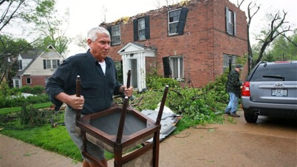 Jim Weiss, from St. Louis, carries out a chair from his friend Roger Schnell's house on Royal Avenue that was severely damaged by a tornado the night before, on Saturday, April 23, 2011, in Ferguson, Mo.