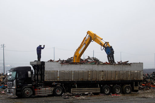 A construction machine loads iron debris on a truck at a devastated area in Minamisanriku, Miyagi Prefecture, northeastern Japan, Saturday, April 23, 2011. (AP Photo/Hiro Komae)