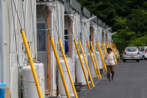 A woman walks by the rows of temporary housings for the March 11 earthquake and tsunami survivors at Hibiki Industrial Park in Higashimatsushima, Miyagi Prefecture, northeastern Japan, Tuesday, June 14, 2011. (AP Photo/Koji Sasahara)
