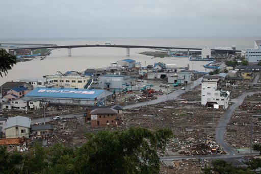 June 27 photo of right side of Kitakami River in Ishinomaki City. Debris was cleared from roads but still remained in the town. Building with blue roof on left is a fish processing factory. (Photo by Kyoritsu Risk Management)