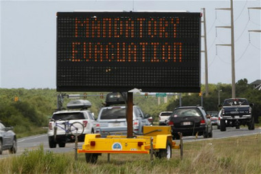 A sign declaring a mandatory evacuation in anticipation of the arrival of Hurricane Irene is seen as motorists head north in Nags Head, N.C., Thursday, Aug. 25, 2011 on North Carolina's Outer Banks. (AP Photo/Charles Dharapak)