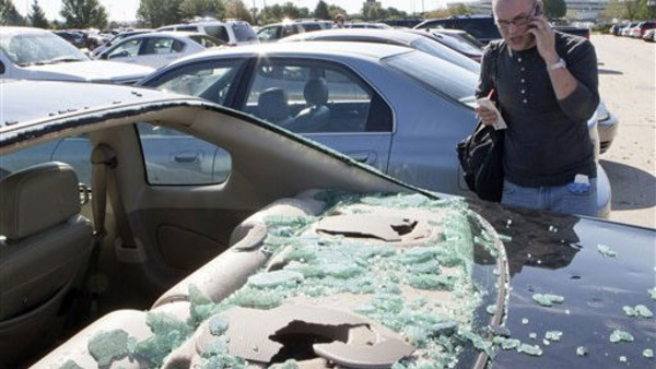 A man calls his insurance company after an August hail storm in Nebraska. The National Crime Insurance Bureau says questionable claims involving hail surged during the first half of 2011. (AP File Photo/Nati Harnik)