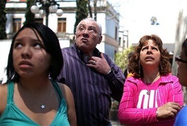 Residents of the Roma neighborhood stand outside their homes after an earthquake was felt in Mexico City, Tuesday, March 20, 2012. (AP Photo/Alexandre Meneghini)