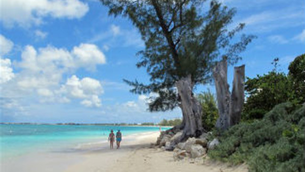 Tourists walk along the beach of Seven Mile Beach in Grand Cayman Island. (AP Photo/David McFadden)