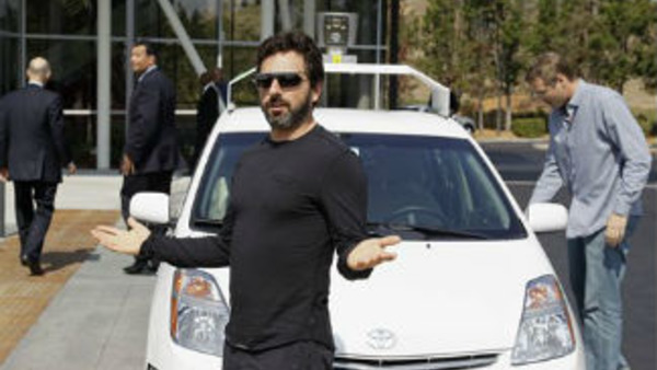 Google co-founder Sergey Brin stands in front of a driverless car (AP Photo/Eric Risberg)