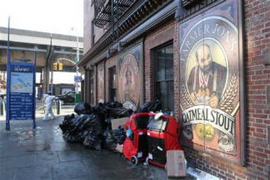 A worker enters the Heartland Brewery at New York's South Street Seaport, as bags of garbage from the Superstorm Sandy cleanup sit out front. (AP Photo/Tina Fineberg)
