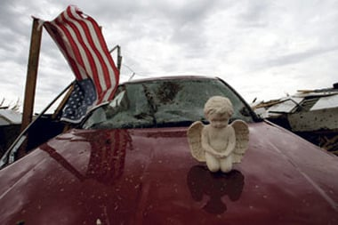 A concrete angel rests on a destroyed car in a tornado-ravaged neighborhood in Moore, Okla. on May 21, 2013. (AP Photo/Charlie Riedel)