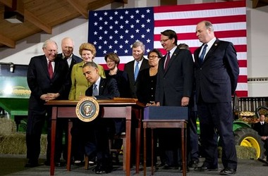 President Barack Obama, surrounded by members of Congress, signs the farm bill. (AP Photo/Jacquelyn Martin)