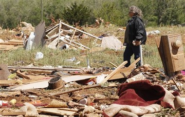 Shelly Hobbie walks through the rubble left of her son's mobile home in Woodward, Okla. on April 15, 2012. (AP Photo/Sue Ogrocki)