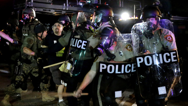A man is detained after a standoff between protesters and police Monday, Aug. 18, 2014, in Ferguson, Mo. (AP Photo/Charlie Riedel)