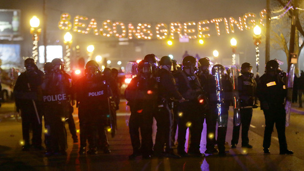 Police gather on the street as protesters react after the announcement of the grand jury decision on Nov. 24 in Ferguson, Mo. (AP Photo/Charlie Riedel)