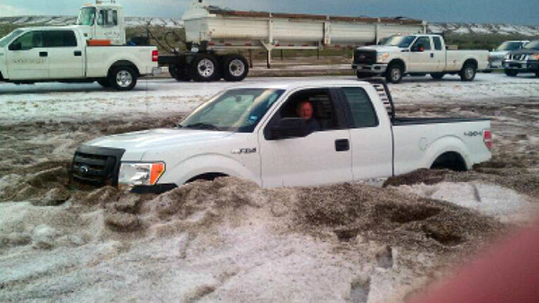 A motorist sits in a truck partially buried in slushy hail near Amarillo, Texas on April 11, 2012. (AP Photo/Courtesy of Amarillo/Potter/Randall Office of Emergency Management)