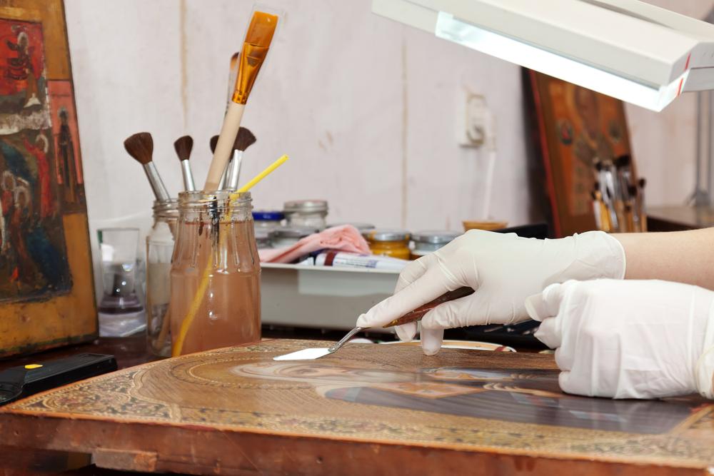 Artist's hand restoring icon