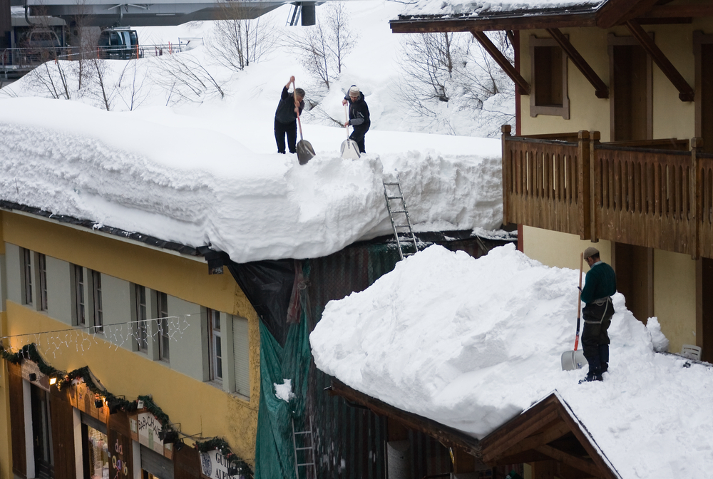 Two men shoveling snow off a roof