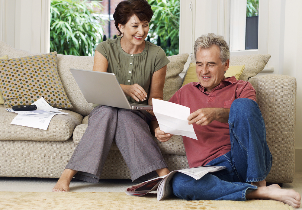 Middle-aged couple looking at bill and using a laptop