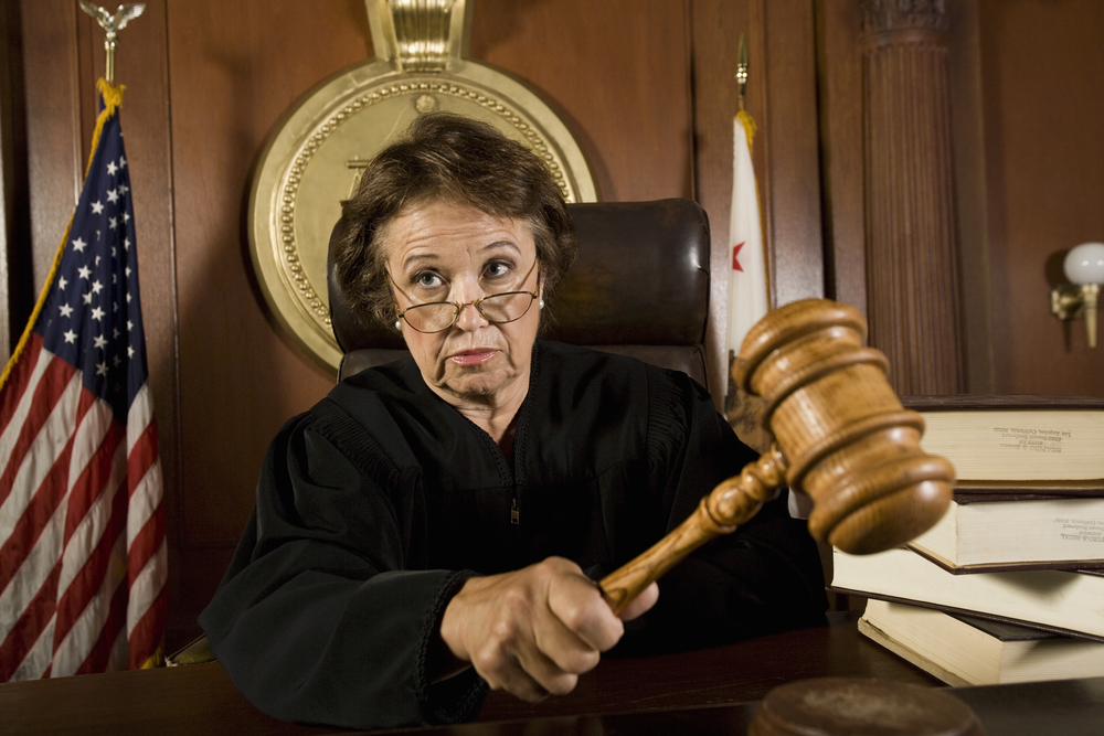 Woman judge banging large gavel