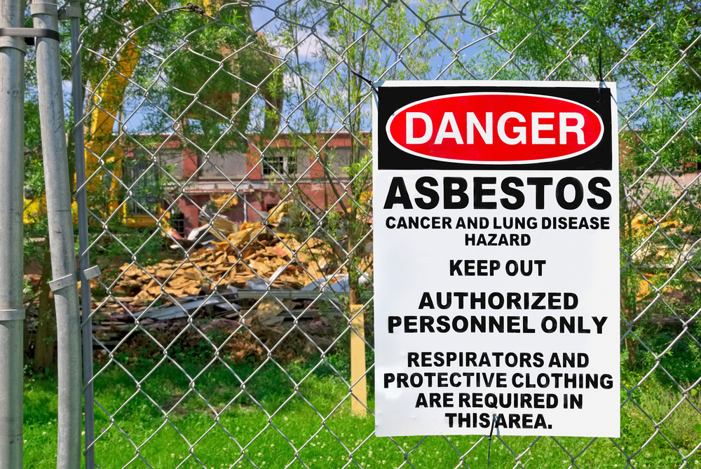 Asbestos removal sign on fence in front of building