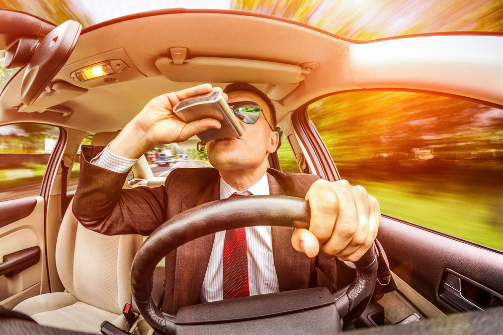 Man drinking from flask behind wheel of car