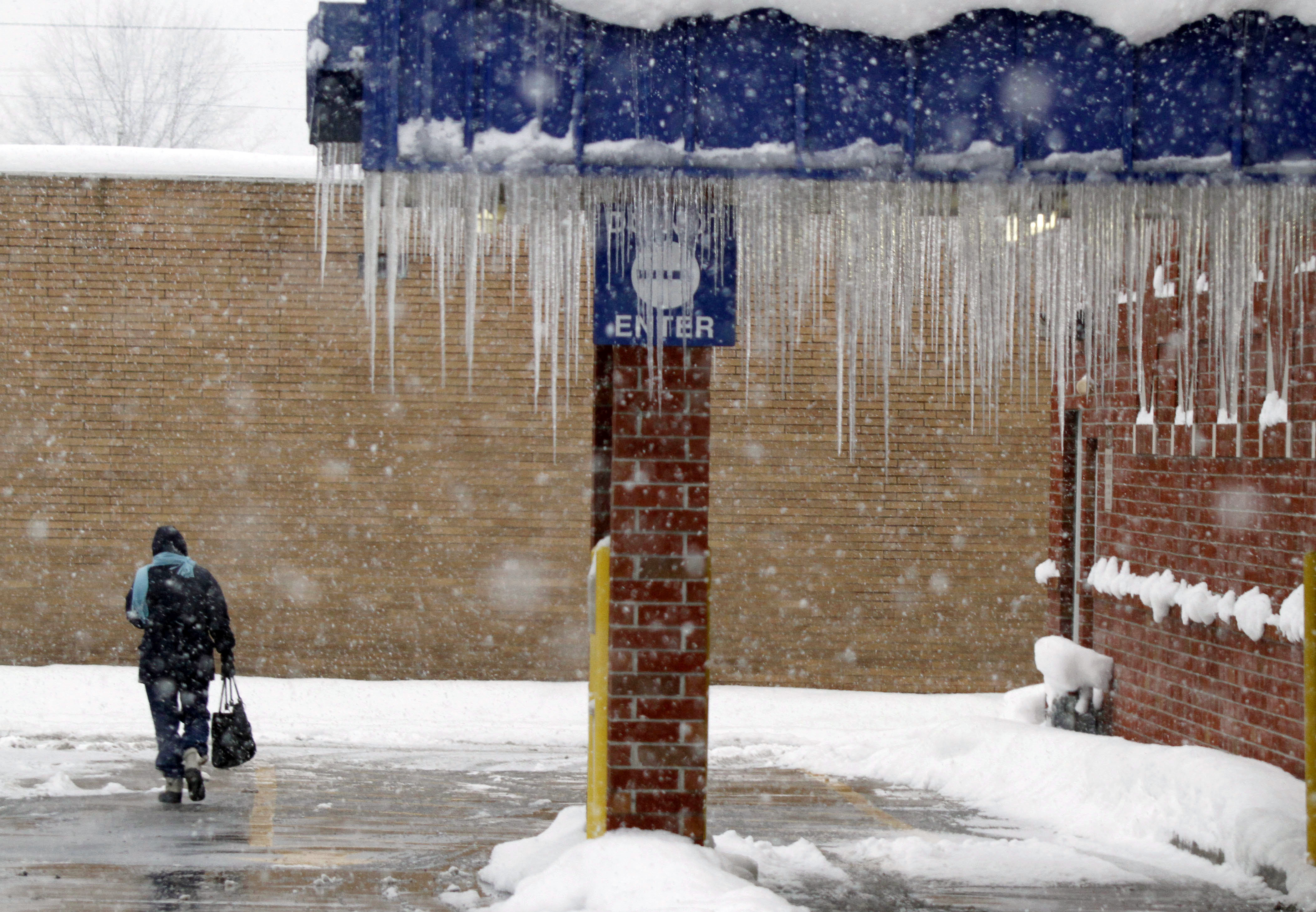Icicles on drive-thru overhang with woman walking