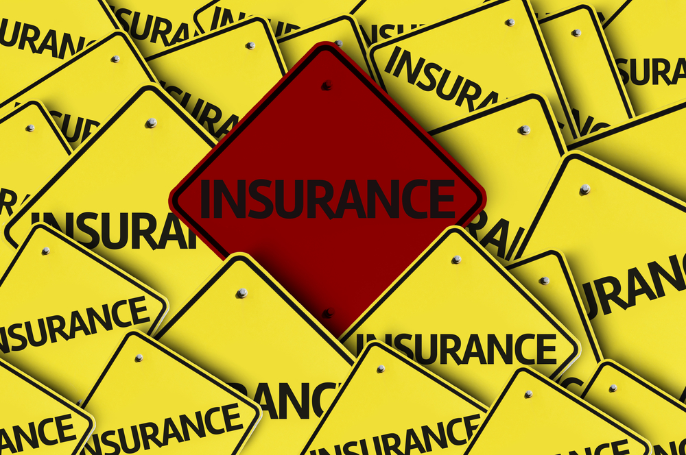 Yellow signs that say insurance with one red sign