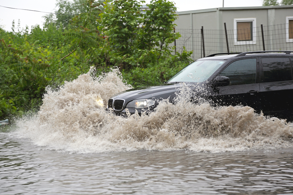 SUV driving through a flooded street