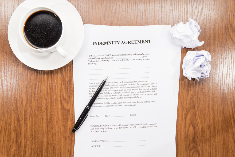 Indemnity agreement on desk with cup of coffee