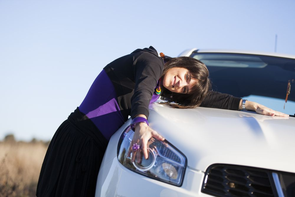 Woman embracing her new car