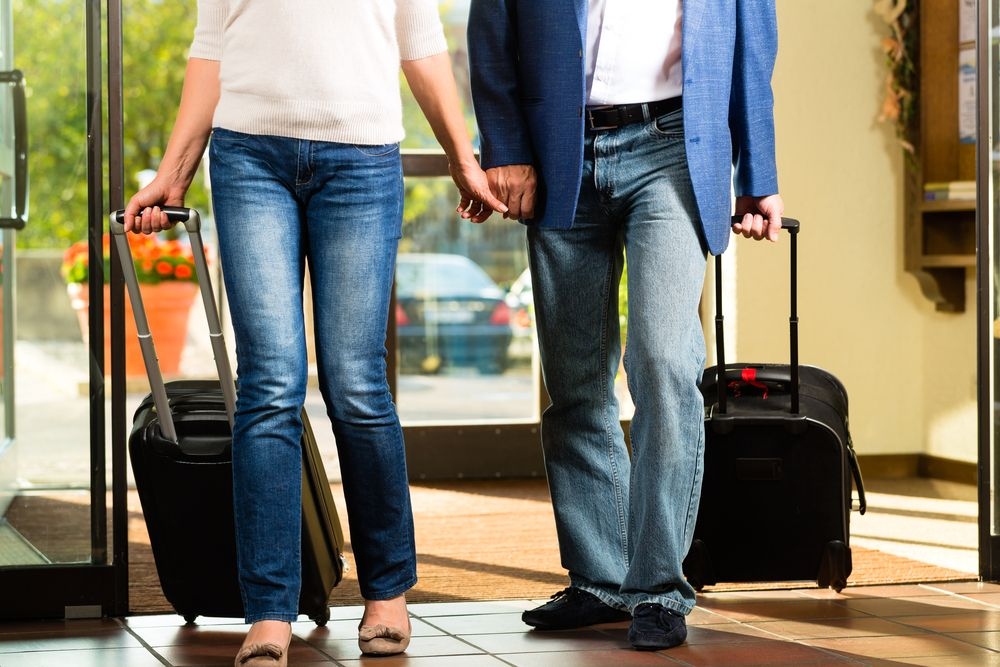 couple walking into a hotel with luggage