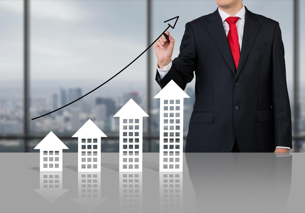 Businessman-drawing-arrow-above-buildings-shutterstock_185810609-Ismagilov
