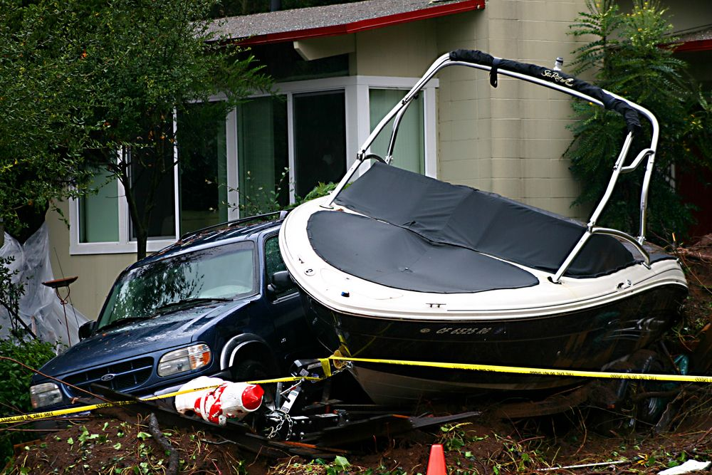 SUV and boat in landslide debris