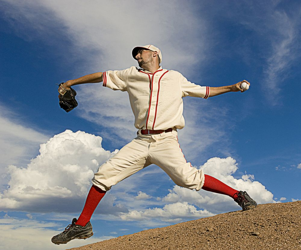 pitcher throwing ball in vintage baseball uniform