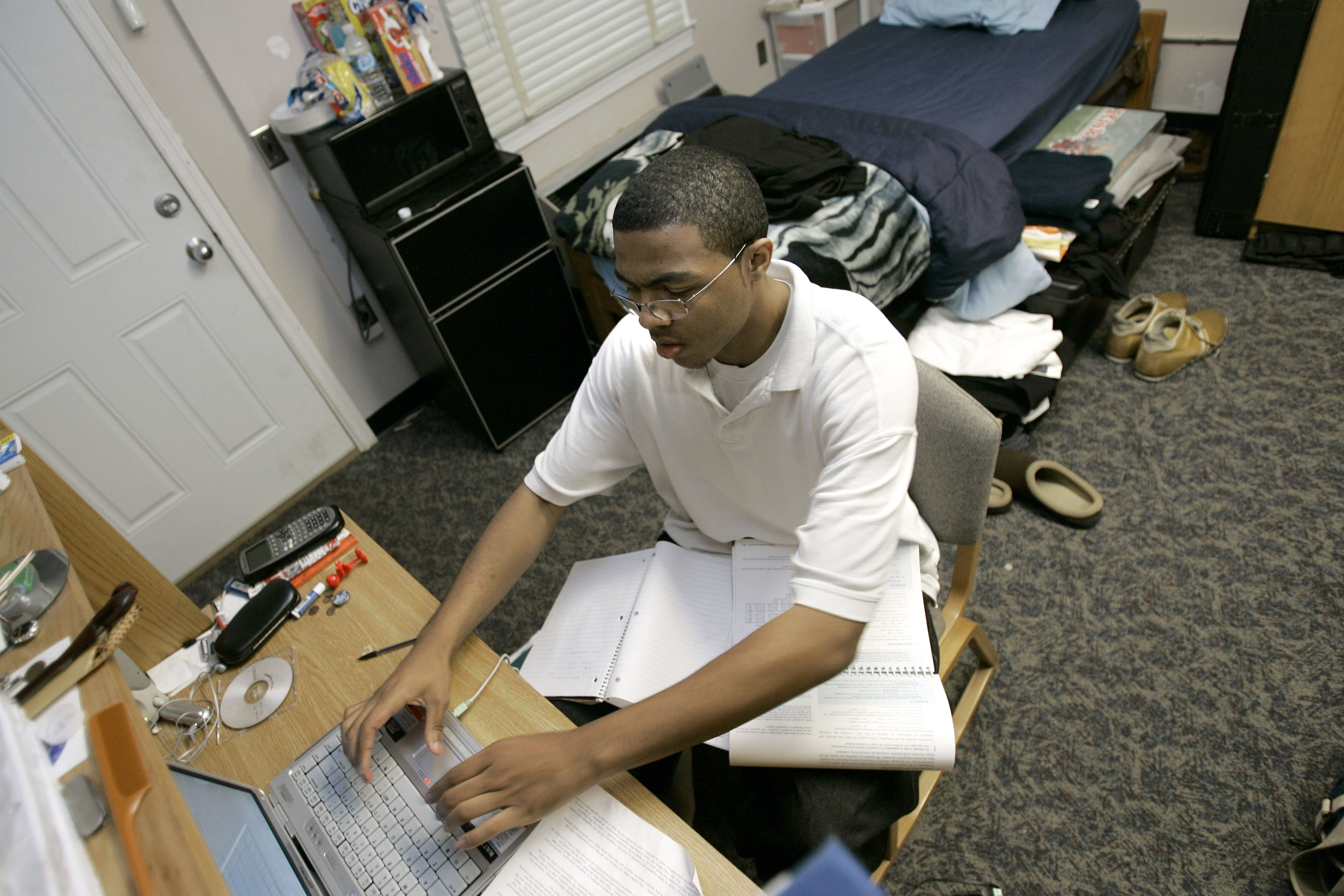 student working on laptop in college dorm room