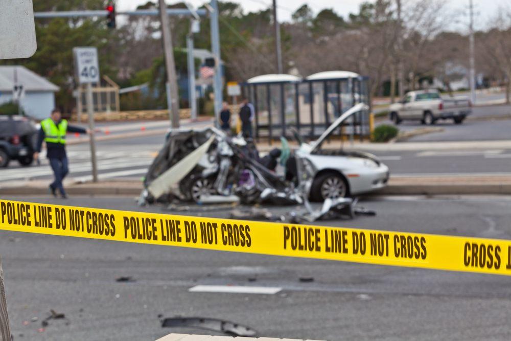 yellow police tape around a car crash