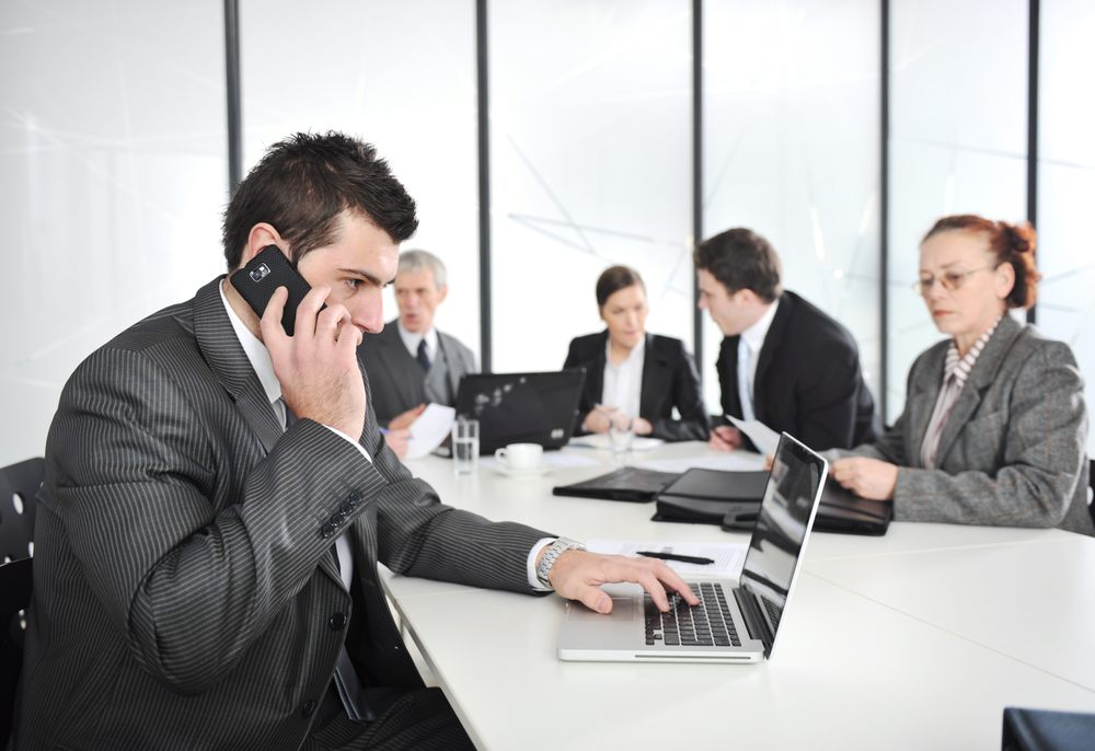 Businessman in conference room talking on cellphone and working on laptop
