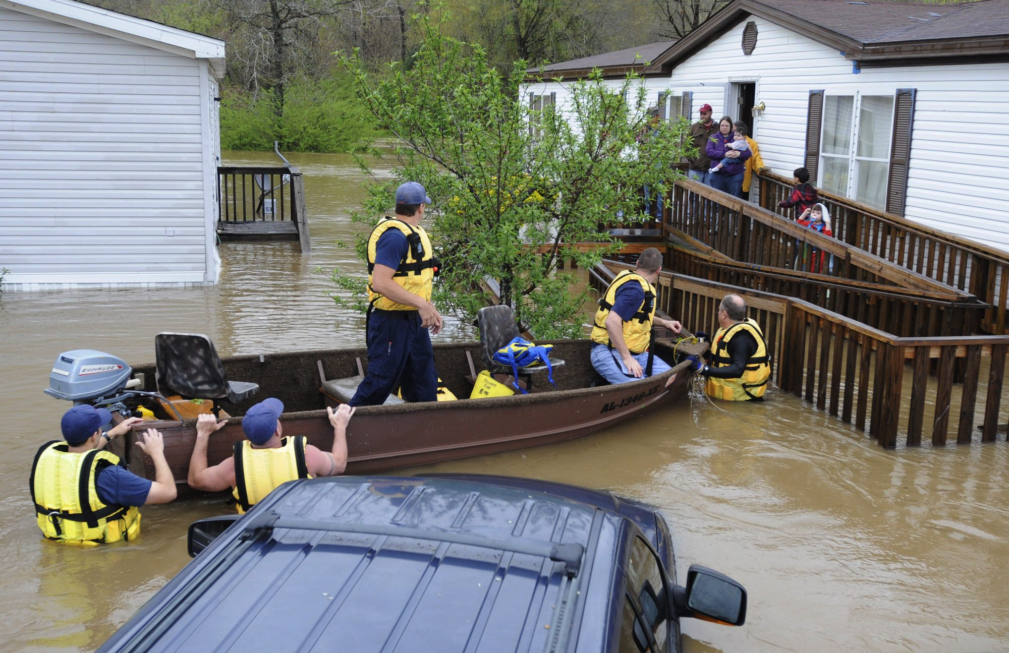 7 Firefighters rescue a family from their home, surrounded by floodwaters, in a mobile home park in Pelham, Ala., on Monday, April 7, 2014.