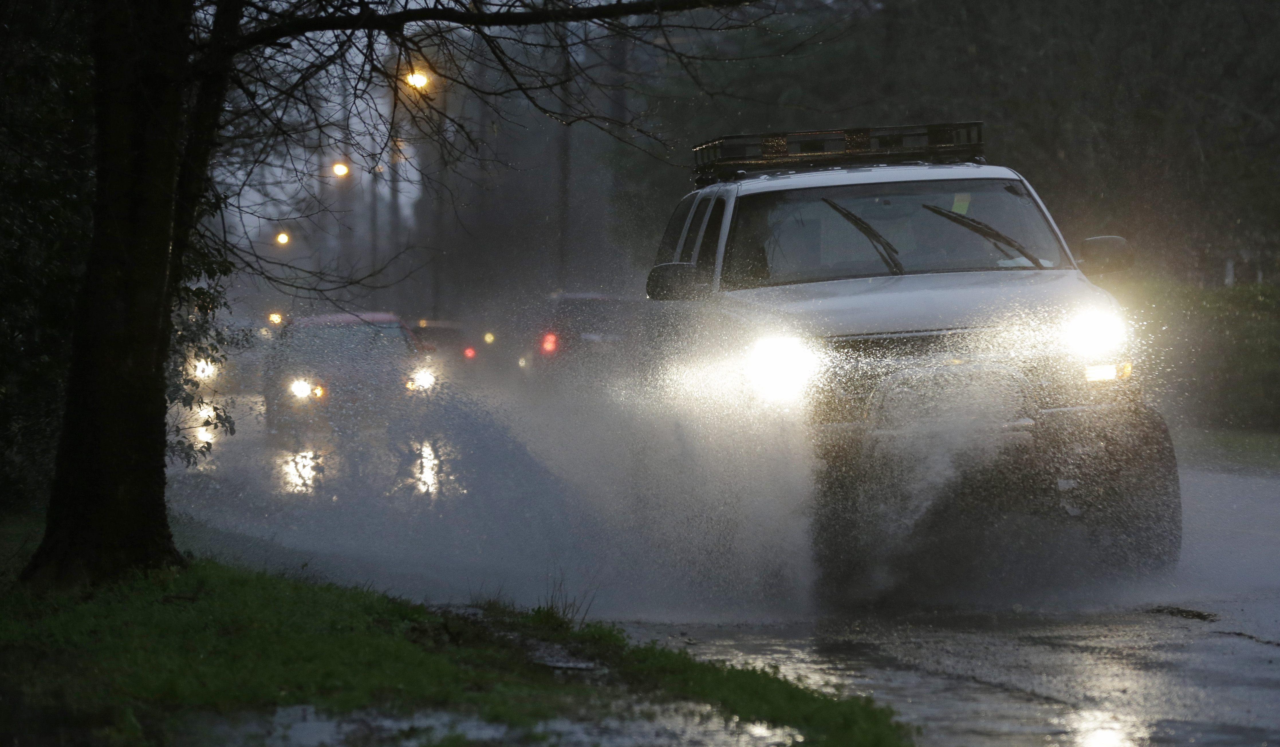 Rush hour traffic drives through minor street flooding in Montgomery, Ala., Tuesday, Feb. 12, 2013.
