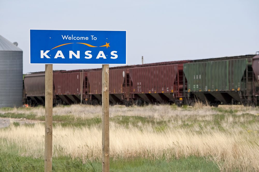 Welcome to Kansas sign with train in background