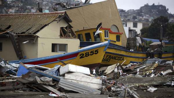 Debris sits among destroyed homes and boats in Coquimbo, Chile, Friday, Sept. 18, 2015. The Chilean government declared a state of emergency for the region around the port city of Coquimbo, near the epicenter of the quake that struck late Wednesday. The magnitude-8.3 earthquake killed 11 people and caused widespread disruption. Hundreds of soldiers were to be sent to the affected region. (AP Photo/Felix Marquez)