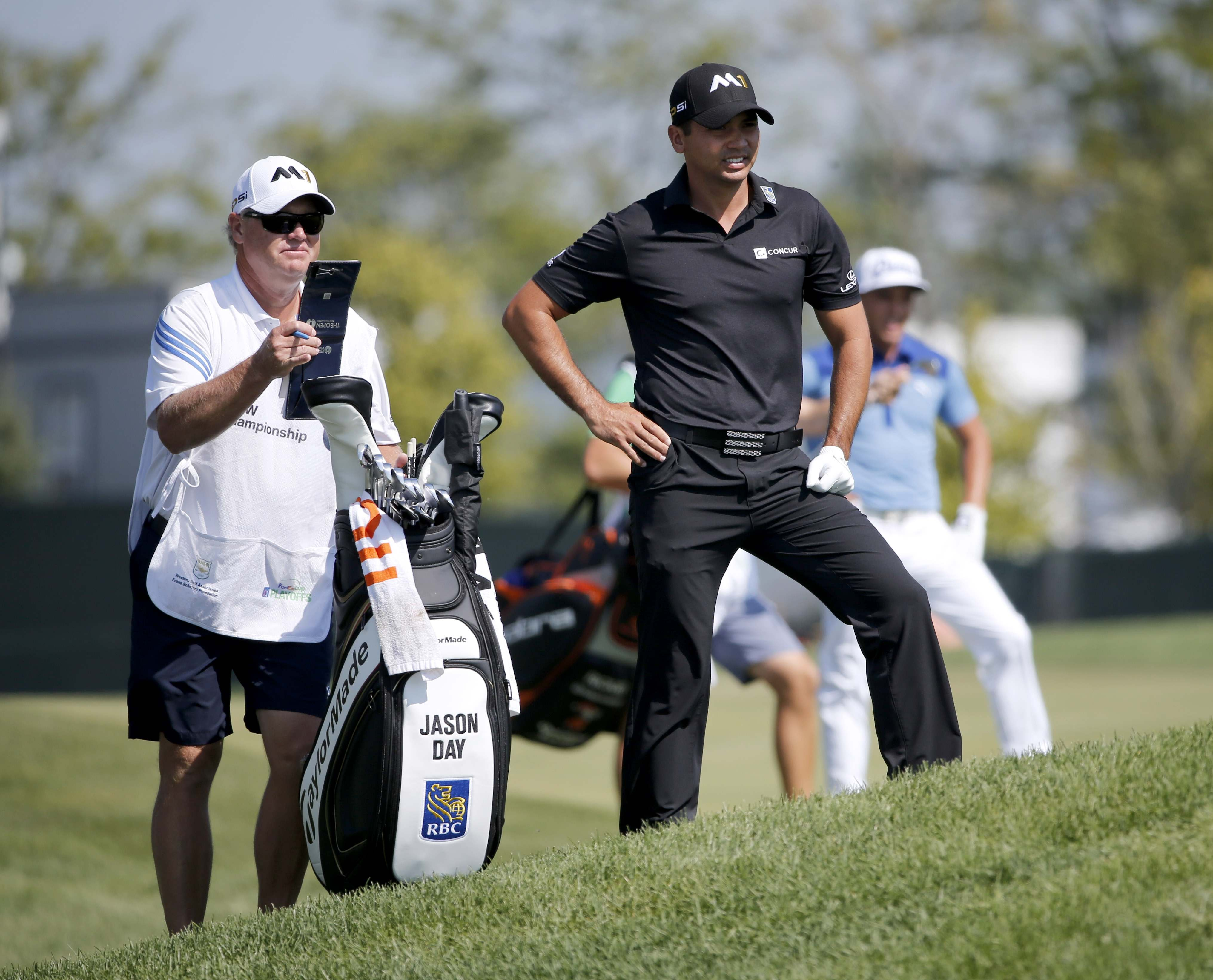 Jason Day, right, of Australia, looks over his shot from the rough with caddie Colin Swatten