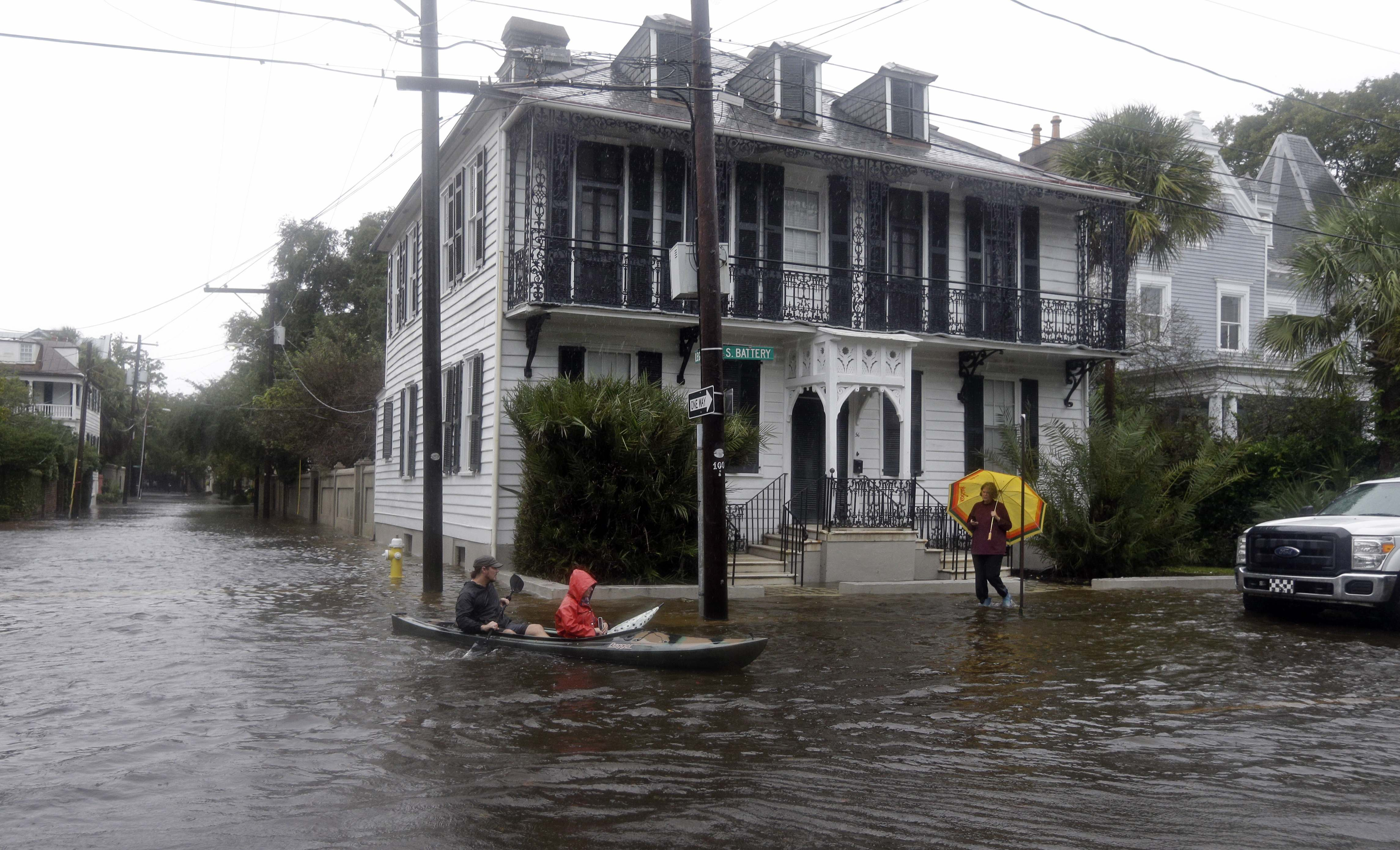 Paul Banker, left, paddles a kayak and his wife Wink Banker, as they takes photos on a flooded street in Charleston, S.C., Saturday, Oct. 3, 2015