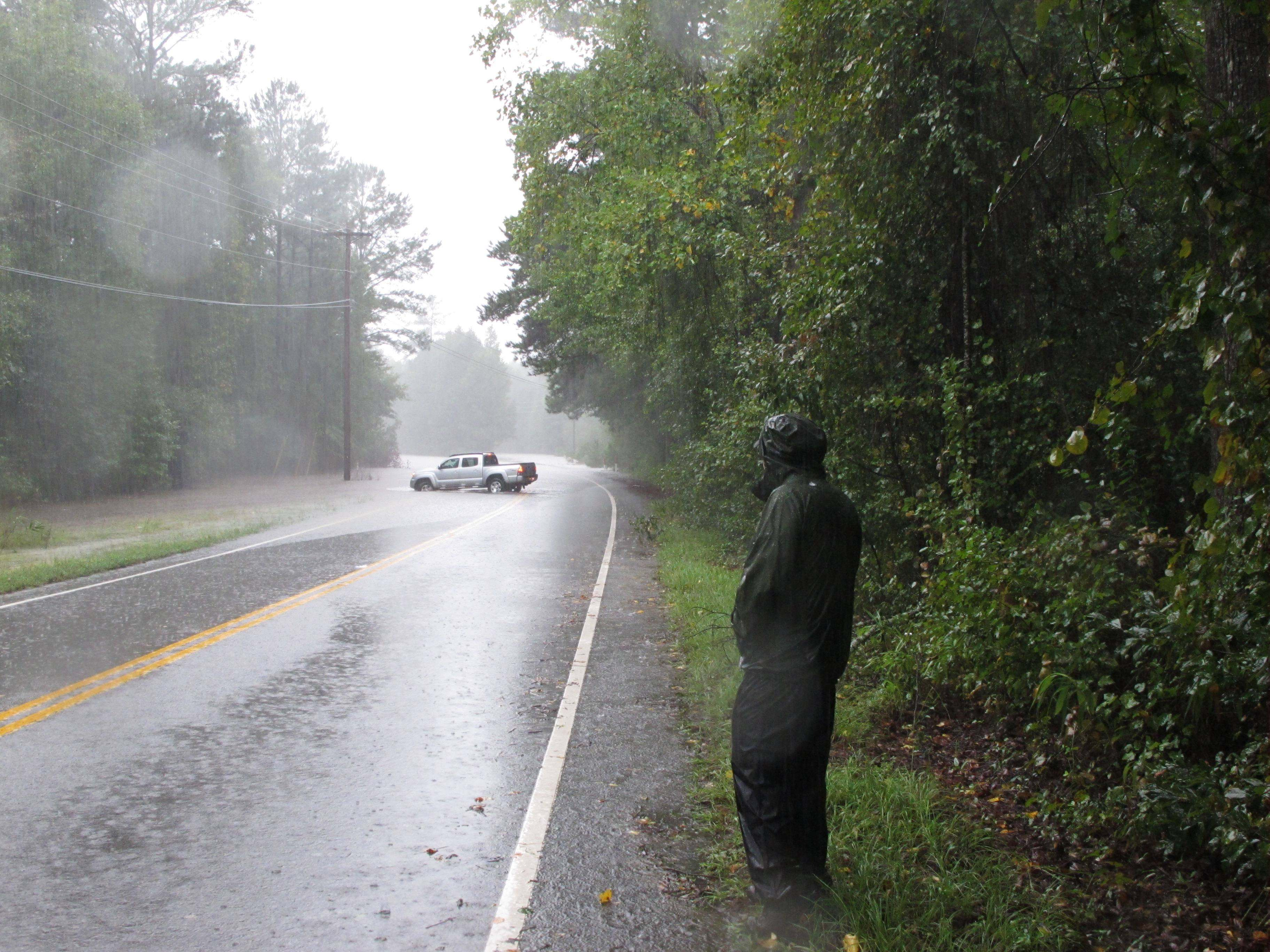 Fred Grooms watches as a car turns around in flood waters on Hardscrabble Road on Sunday, Oct. 4, 2015, in Columbia, S.C.