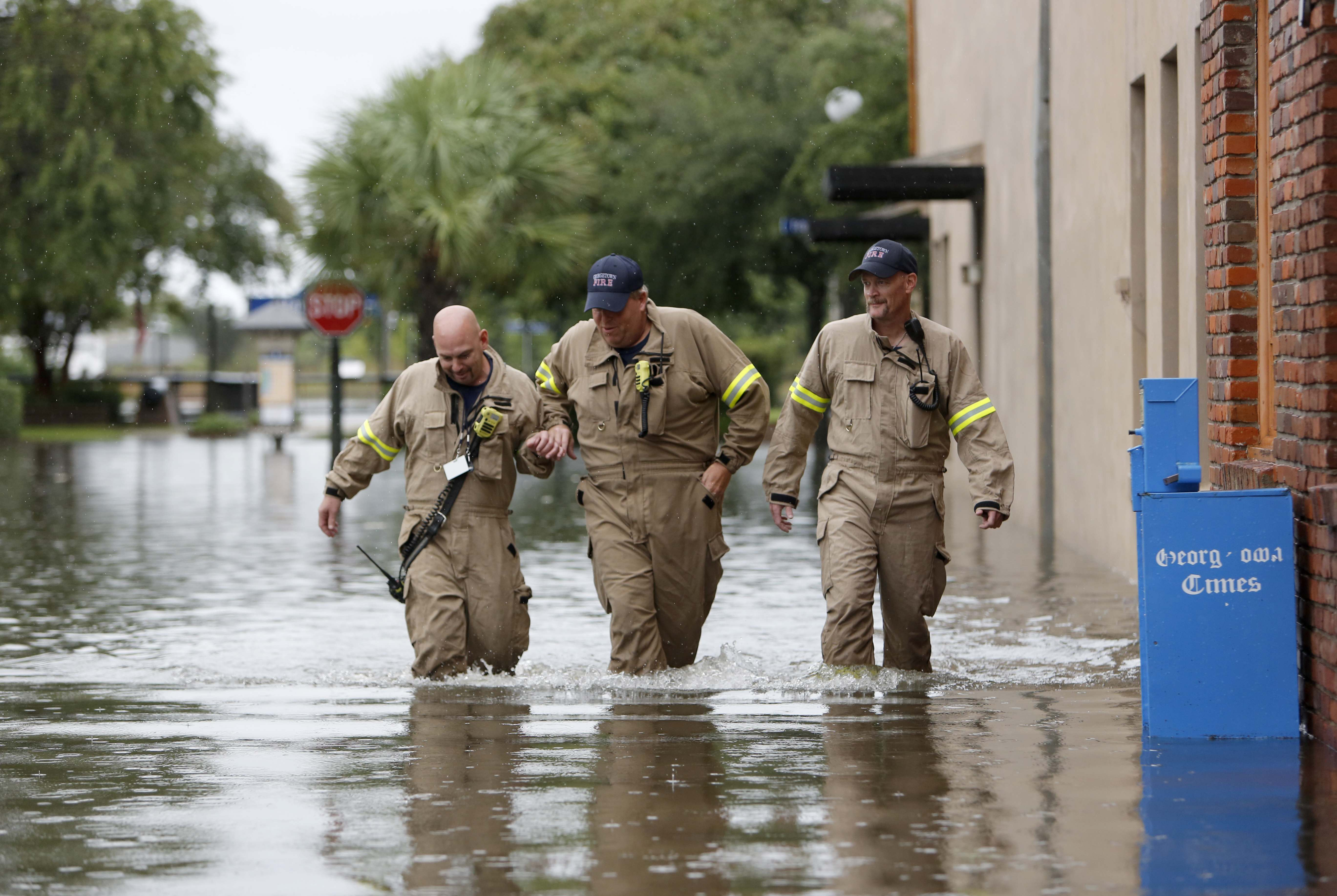 Firemen, from left to right, Norman Beauregard, Kevin Ettenger and Chris Rodgers with the Georgetown Fire Department, inspect the flood waters at high tide in the historic downtown in Georgetown, S.C., Sunday, Oct. 4