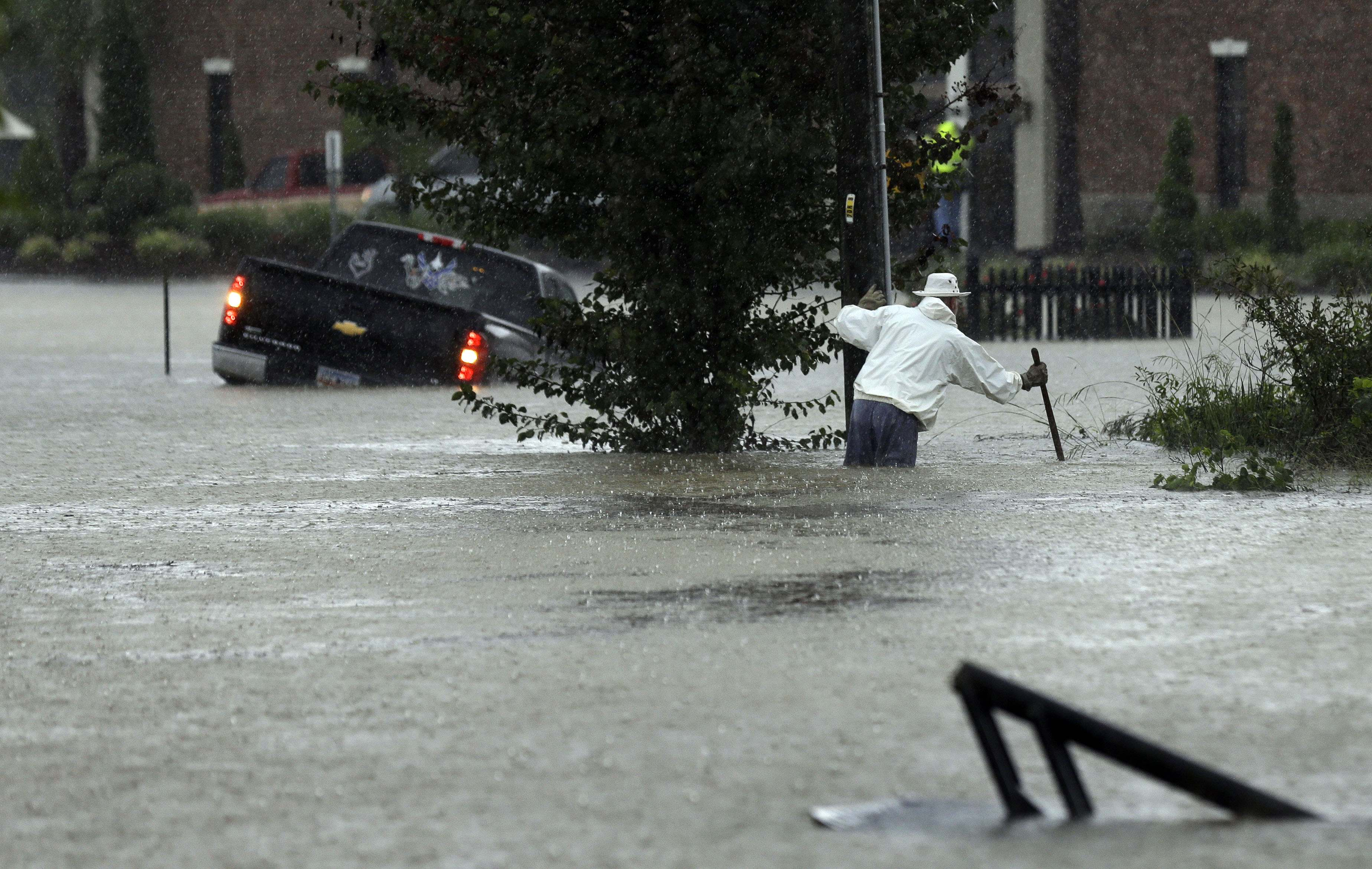 A vehicle and a man try to navigate floodwaters in Florence, S.C., Sunday, Oct. 4, 2015, as heavy rain continues to cause widespread flooding